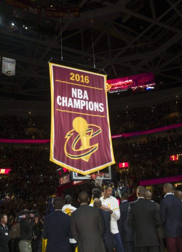Cleveland Cavaliers players and executives watch the championship banner being raised before a basketball game against the New York Knicks in Cleveland, Tuesday, Oct. 25, 2016. (AP Photo/Phil Long)