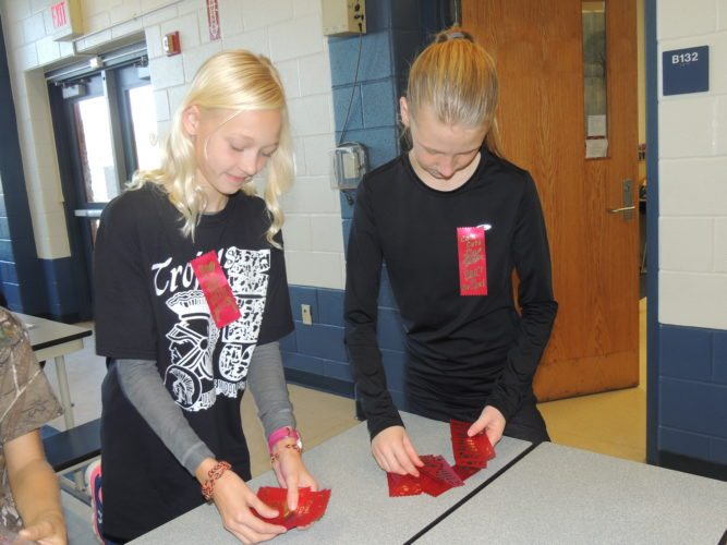 Photo by Drew Parker Students Against Destructive Decisions club members Audrey Robinson, left, and Sierra Taylor prepare materials for Red Ribbon Week at Moundsville Middle School.