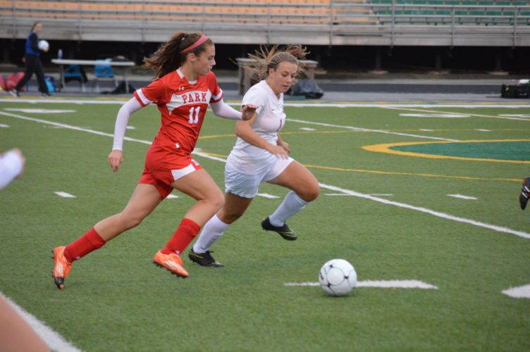 Photo by Josh Strope Wheeling Park's Morgan Glass (11) moves the ball upfield as University's Emma Sizer (1) defends.