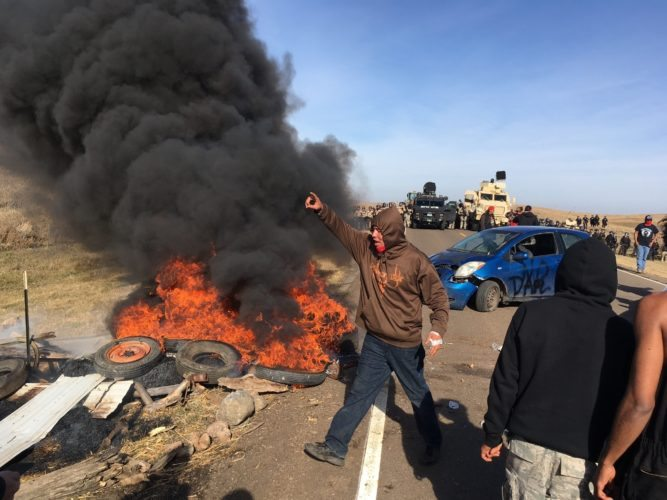 Demonstrators stand next to burning tires as armed soldiers and law enforcement officers assemble on Thursday, Oct. 27, 2016, to force Dakota Access pipeline protesters off private land where they had camped to block construction. The pipeline is to carry oil from western North Dakota through South Dakota and Iowa to an existing pipeline in Patoka, Ill. (Mike McCleary/The Bismarck Tribune via AP)