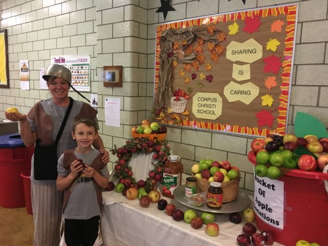 Corpus Christi School faculty member Shannon Tucker Wall, attired as Johnny Appleseed, and student Dawson Huggins  promote consumption of apples as part of healthy eating.  Photos  Provided