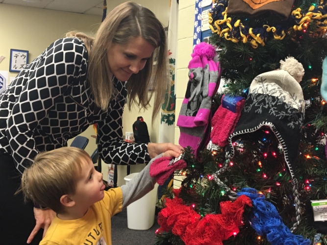 Photo Provided Woodsdale Elementary School Principal Ashlea Minch helps student Ben Eikey place his donation on the school's Mitten Tree. Donations to the Woodsdale Mitten Tree will help provide those in need with warm clothes this winter.