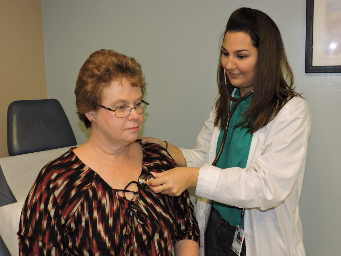 Photo by Casey Junkins Dr. Jennifer Calafato, an internal medicine physician at Ohio Valley Medical Center, examines patient Janice Carenbauer at Wheeling Health Right.