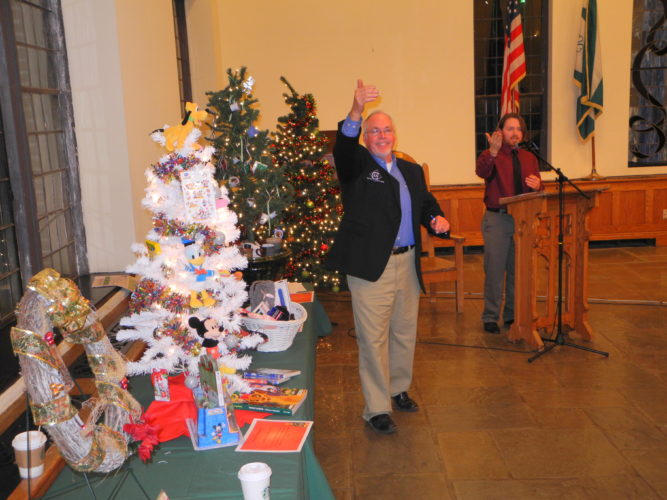 Photo by Warren Scott Auctioneers Harry Grafton, left, and Clint Chevalier of Gary W. Cain Realtors take bids on nearly two dozen Christmas trees of various sizes and themes and several wreaths and gift baskets at an auction Thursday at Bethany College that raised $4,430 for Bernie's Kids, a local toy drive for Brooke County children in need.