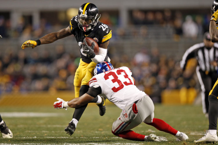 Pittsburgh Steelers running back Le'Veon Bell (26) runs throw a tackle by New York Giants free safety Andrew Adams (33) during the first half of an NFL football game in Pittsburgh, Sunday, Dec. 4, 2016. (AP Photo/Jared Wickerham)