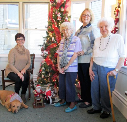 Photo Provided Preparing for the annual Victorian Christmas Tour at Elmhurst, The House of Friendship, in Wheeling are, from left, Jamie Crow, executive director; resident Betsy Higgins; Paula Coats, resident assistant who is in charge of the holiday decorating; and resident Blanche Wakim. Also shown is Elmhurst's new house dog, Goldie.