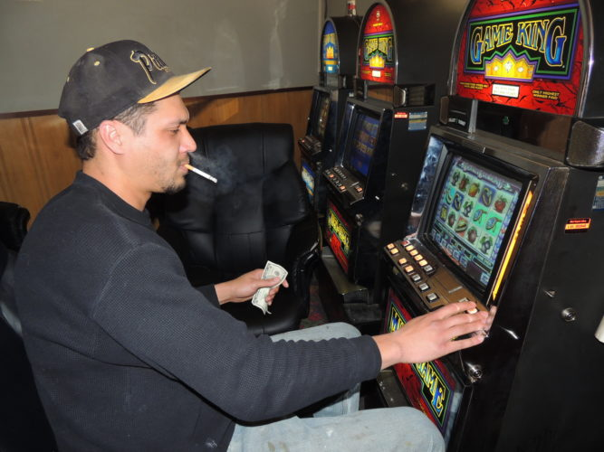 File Photo Chivas Webb of Wheeling smokes while gambling at a downtown limited video lottery parlor.