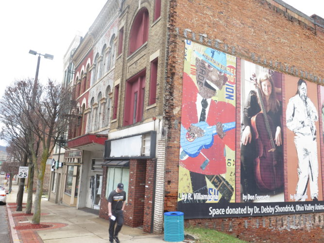 Photo by Alec Berry A pedestrian passes by 1107 and 1109 Main St. in downtown Wheeling on Thursday.