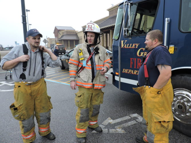 Photo by Janet Metzner Valley Grove  Volunteer Fire Department Chief Scott Himrod,  center, and  firefighters Craig Blacker, left, and Chris Oliver, finish up a call at  Walmart at The Highlands on Jan. 2 after a vehicle fire spread to  multiple vehicles.
