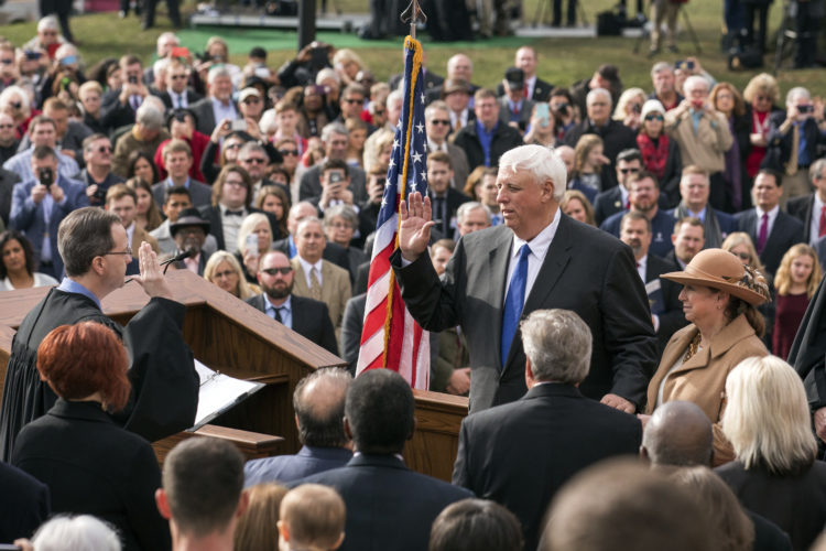 West Virginia Gov. Jim Justice, right of center, takes the oath of office administered by state Supreme Court Chief Justice Allen Loughry II, Monday, Jan. 16, 2017, in Charleston, W.Va. Justice is joined by his wife, Cathy. (AP Photo/Walter Scriptunas II)