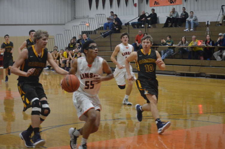 Linsly's Malachi Onwuka drives in for a layup as Cameron's Robert Milliken (32) and Hunter Aston (10) chase him down.