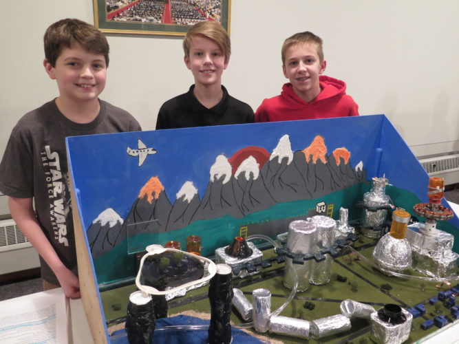 Photo by Alec Berry Triadelphia Middle School students Gavin Minder, from left, Kaden Schreiber and Noah Seivertson pose with their entry in the Future Cities competition Thursday.