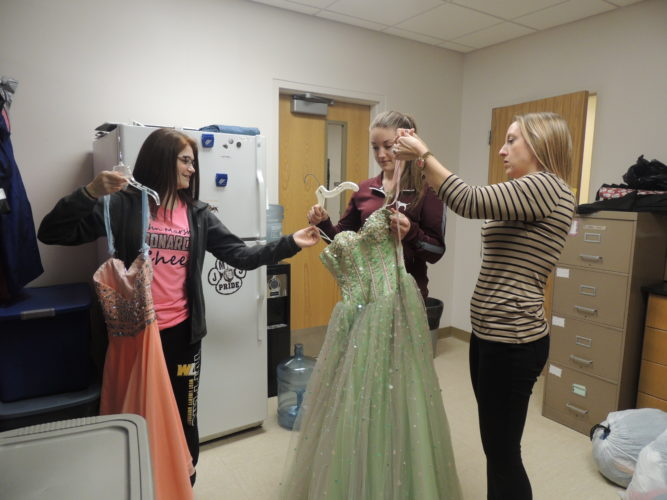 Photo by Drew Parker John Marshall High School Paws for a Cause advisor Marcie Robbins sorts through donated formal dresses with student members Jourdin Yuncke, left, and Kailey Pettit.