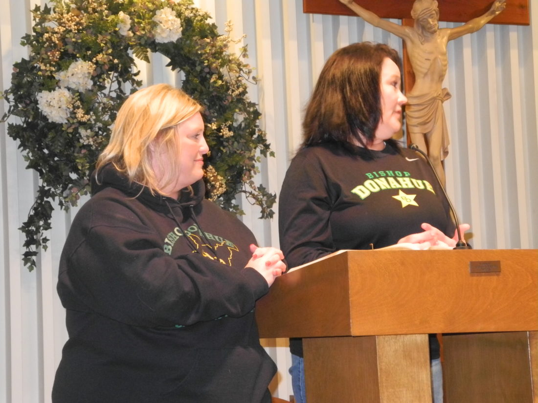 Anna Lehew, left, and Theresa Gretchen, parents of Bishop Donahue High School students, speak            during a rally Saturday in support of the school, which officials of the Roman Catholic Diocese of Wheeling-Charleston announced Thursday will close at the end of the               academic year.  Photo by Ian Hicks