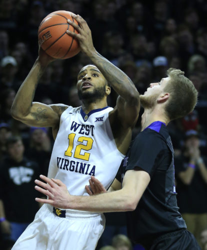 West Virginia guard Tarik Phillip (12) clips the chin of Kansas State forward Dean Wade (32) while shooting during the first half of an NCAA college basketball game in Manhattan, Kan., Saturday, Jan. 21, 2017. (AP Photo/Orlin Wagner)