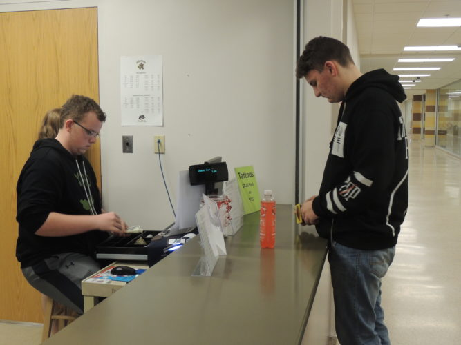 Photo by Drew Parker John Marshall High School junior and Monarch Industries employee Louis Yoho sells a drink to sophomore Jackson Palkovic.