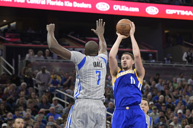 Golden State Warriors guard Klay Thompson (11) goes up for a shot in front of Orlando Magic forward Serge Ibaka (7) during the first half of an NBA basketball game in Orlando, Fla., Sunday, Jan. 22, 2017. (AP Photo/Phelan M. Ebenhack)