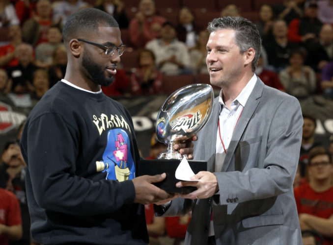Teddy Greenstein, right, a sportswriter for the Chicago Tribune, presents Ohio State quarterback J.T. Barrett with the Chicago Tribune Silver Football Award during the first half of an NCAA college basketball game between Northwestern and Ohio State, Sunday, Jan. 22, 2017, in Columbus, Ohio. (AP Photo/Jay LaPrete)