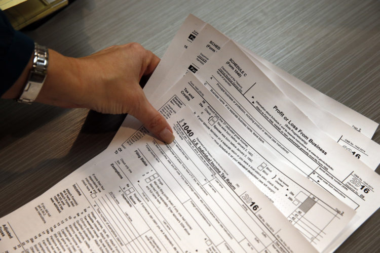 In this Jan. 14, 2017, photo, tax professional and tax preparation firm owner Alicia Utley reaches for hard copies of tax forms while working to stay caught up on a Saturday at the start of the tax season rush, in her offices at Infinite Tax Solutions, in Boulder, Colo. The IRS will begin accepting returns on Jan. 23, and tax experts recommend that Americans continue to file their returns early. (AP Photo/Brennan Linsley)