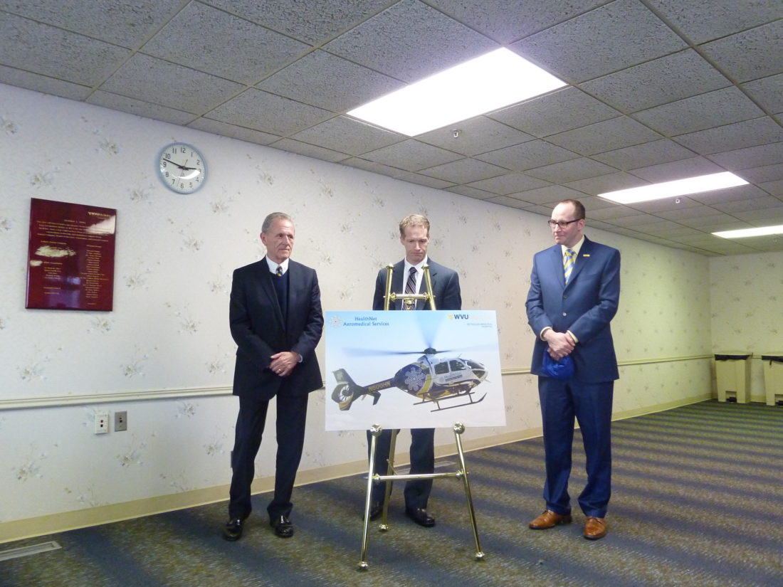 Unveiling a  photograph of the HealthNet Aeromedical  Services  helicopter, from left, are Bernard Twigg, board  president of WVU  Medicine Reynolds Memorial Hospital; Dr. David Hess, CEO of WVU  Medicine Reynolds, and Albert Wright,  president and CEO of West Virginia University Health System.