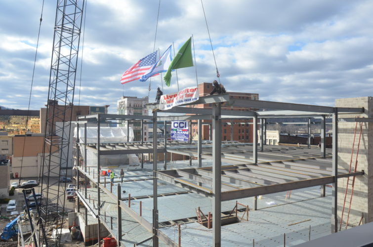 Photo by Scott McCloskey Contractors working on The Health Plan's new headquarters in downtown Wheeling place the final beam of the structure's steel frame Monday.