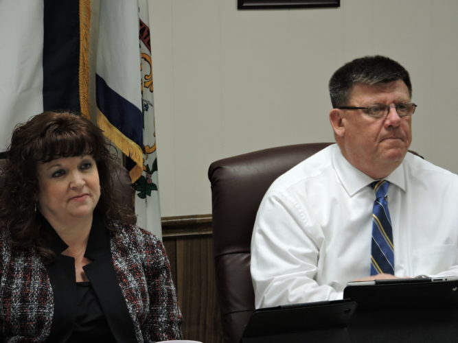 File Photo by Alan Olson Former Marshall County Board of Education President Beth Phillips, left, attends a prior meeting as Vice President Thomas Gilbert looks on.