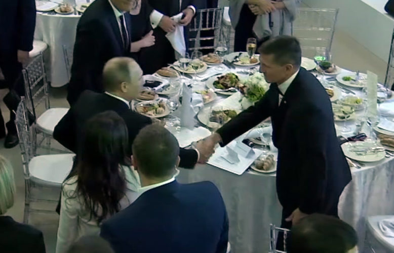In this image made from a video taken on Dec. 10, 2015 and made available on Tuesday, Feb. 14, 2017, US President Donald Trump's former National Security Advisor Michael Flynn, right, shakes hands with Russian President Vladimir Putin, in Moscow. Flynn, who resigned following reports that he misled White House officials about his contacts with Russia, was seen attending the 10th anniversary of the Russian television network RT in 2015 where Russian President Vladimir Putin gave a speech. A US official has told The Associated Press that Flynn was in frequent contact with Ambassador Sergey Kislyak on the day the Obama administration imposed sanctions on Russia after US intelligence reported that Russia had interfered with the US elections. (Ruptly via AP)