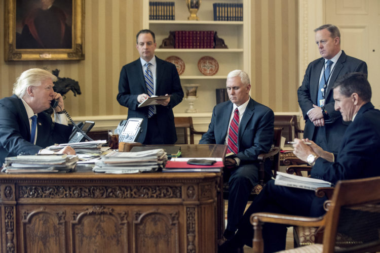 FILE - In this Jan. 28, 2017 file photo, President Donald Trump accompanied by, from second from left, Chief of Staff Reince Priebus, Vice President Mike Pence, White House press secretary Sean Spicer and then-National Security Adviser Michael Flynn speaks on the phone with Russian President Vladimir Putin, in the Oval Office at the White House in Washington. Trump's White House is nearly paralyzed by crisis, divisions and dysfunction. Virtually all policy announcements have slowed to a crawl. Aides are undercutting each other in leaks (AP Photo/Andrew Harnik, File)