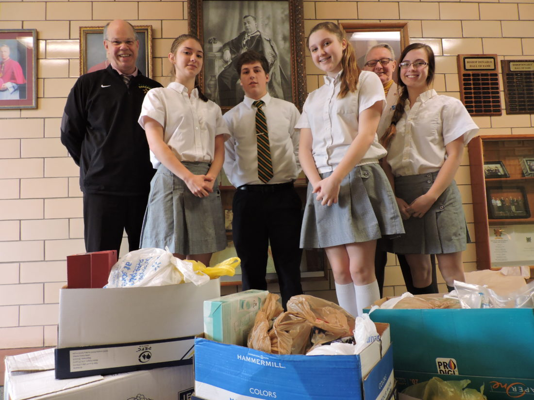 Photo by Alan Olson At rear are Bishop Donahue High School Principal Tom Wise, left, and Pat Duffy, who is involved with various veterans projects. From left front are students Ally Berletch, Nathan Rush, Kendra Dobbs and Tessa Bower and some of the many boxes of clothes they collected.