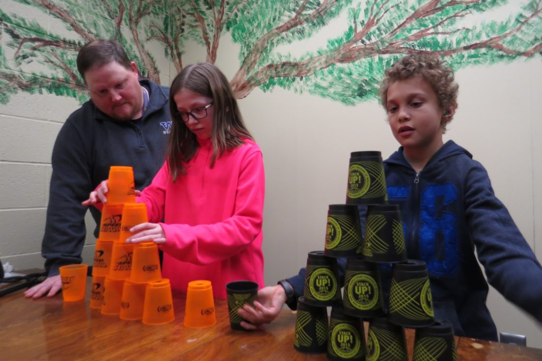 Photo Provided During a recent practice session at Woodsdale Elementary School in Wheeling, health and physical education teacher Michael Cook coaches the cup stacking techniques of fourth-graders Maggie Hupp and Daevon Dukes. The two are among 40 competing in the fifth annual Ohio Valley Sport Stacking Championships at the school Saturday morning. The event is a qualifier for the Amateur Athletic Union's Junior Olympic Games, which will take place in Detroit in July.