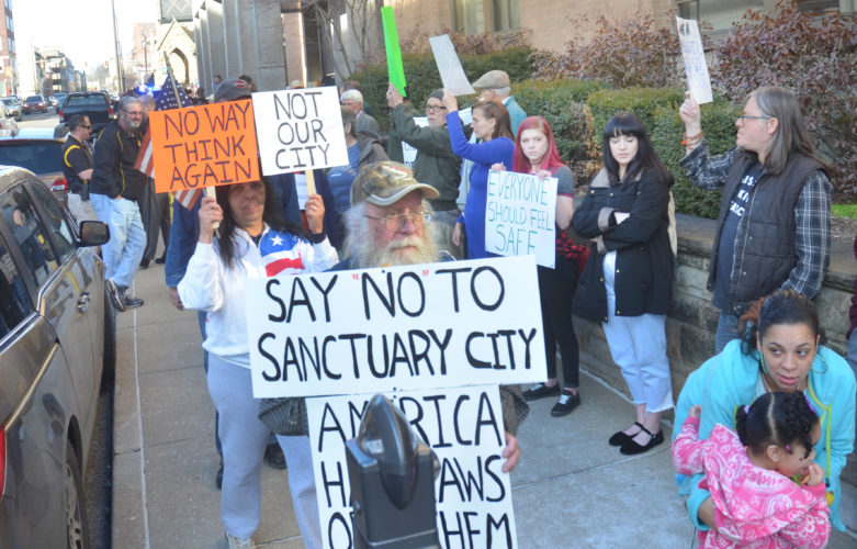 Photos by Scott McCloskey Opposing views on immigration are represented Friday during a demonstration in Wheeling.