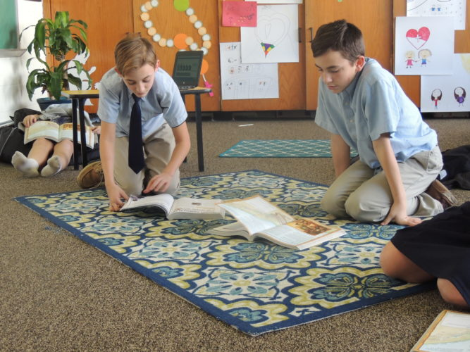 Photo by Drew Parker All Saints School students Elijah Young, left, and Lorenzo Ferrera read during religion class.