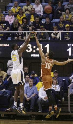 West Virginia forward Lamont West (15) shoots over Texas guard Eric Davis Jr. (10) during the first half of an NCAA college basketball game, Monday, Feb. 20, 2017, in Morgantown, W.Va. West Virginia defeated Texas 77-62. (AP Photo/Raymond Thompson)