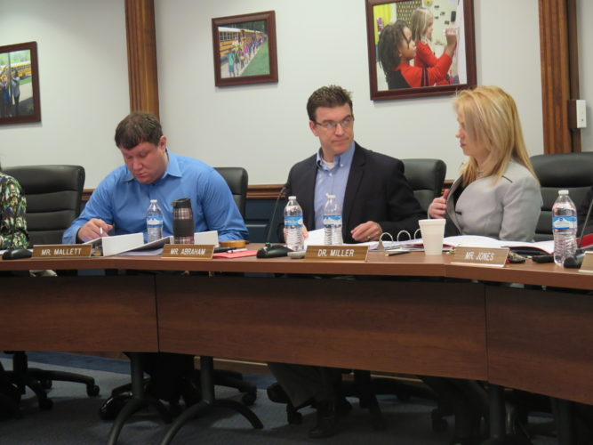 Photo by Joselyn King Ohio County Board of Education member Shane Mallett, left, and Board President Zach Abraham review matters with Superintendent Kim Miller at the start of today's special board meeting to take actions regarding personnel.