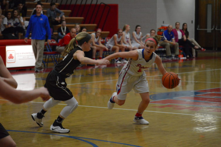 Wheeling Park's Kylie McKennen (5) dribbles down court while John Marshall's Abby Blake defends.  Photo by  Kyle Lutz