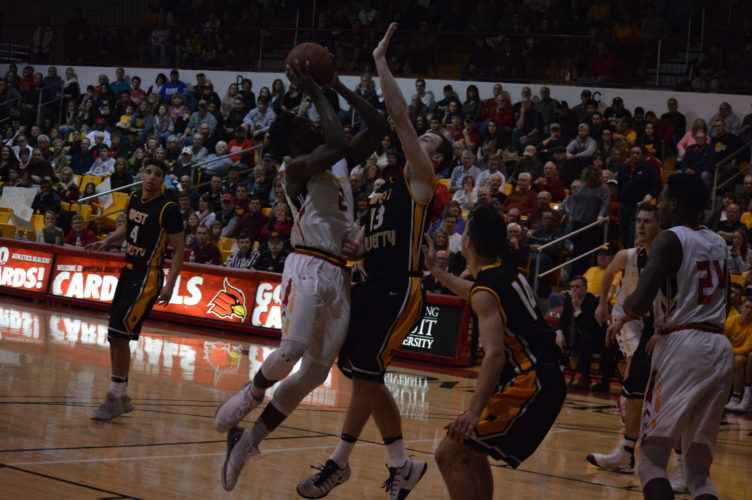 Photo by Cody Tomer Wheeling Jesuit's Pat Moseh (2) goes up for a shot as West Liberty's James Griffin (13) goes for the block Saturday at the McDonough Center.