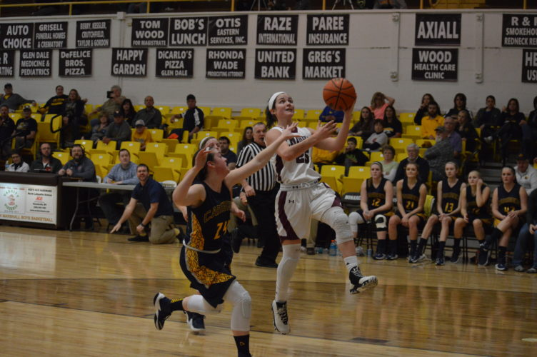 Wheeling Central's Taylor Duplaga (25) goes in for a layup as Cameron's Jordyn Hughes defends.  Photo by  Cody Tomer