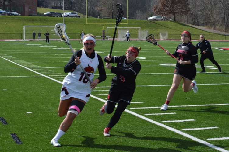 Photo by Cody Tomer Above: Wheeling Jesuit's Markie Wright (16) attempts to get around Roberts Wesleyan's Maddi Chille (5) during Sunday's NCAA lacrosse action at Wheeling Jesuit.