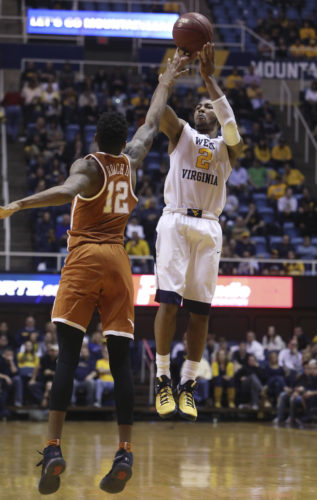 West Virginia guard Jevon Carter (2) shoots while being guarded by Texas guard Kerwin Roach Jr. (12) during the second half of an NCAA college basketball game, Monday, Feb. 20, 2017, in Morgantown, W.Va. West Virginia defeated Texas 77-62. (AP Photo/Raymond Thompson)