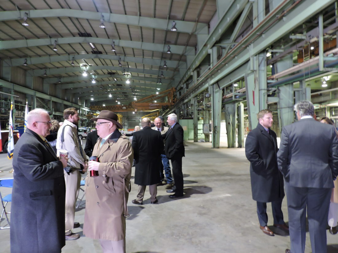 Photo by Craig Howell Local and state officials and other guests gather in the former ArcelorMittal Steel machine shop in the north end of Weirton Friday to hear about plans by Bidell Gas Compression to open operations at the dormant facility.