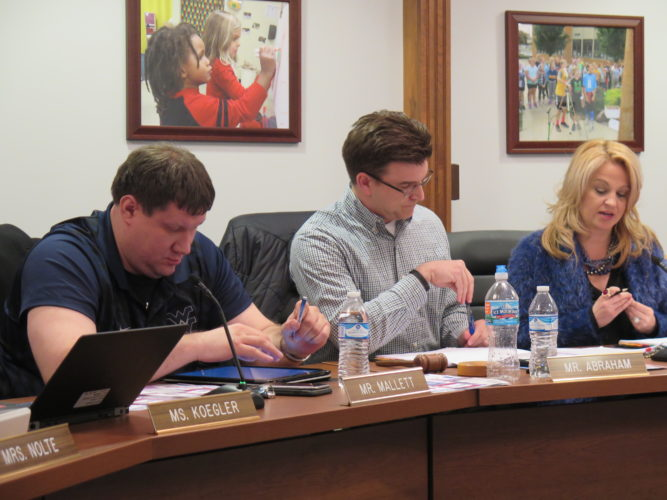 Photo by Joselyn King Ohio County Board of Education member Shane Mallett, left, board President Zach Abraham and Superintendent Kim Miller listen during Thursday night's board meeting.
