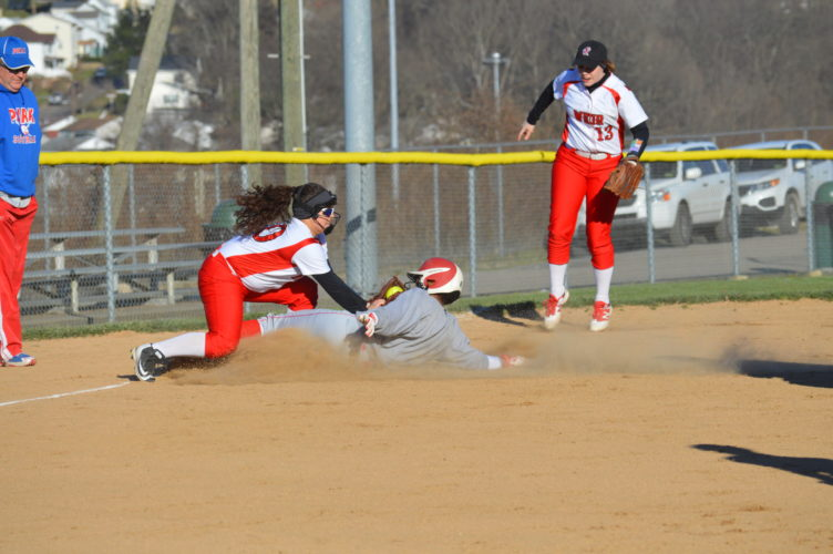 Photo by Kyle Lutz Wheeling Park's Ateria Walker slides under a tag attempted by Weir's Sarah Bodrog during Wednesday's game.
