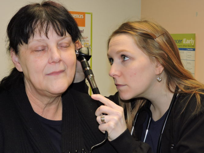 Photo by Casey Junkins Amanda Cummins, right, a physician's assistant at Wheeling Health Right, examines patient Tina Serevics. The free clinic received $20,000 worth of federal Community Development Block Grant money this year to help purchase medication.