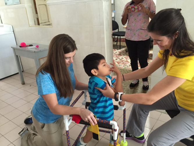 Photo Provided During their service trip to Merida, Mexico in January, Nicole McLain and Jessica Roche, two Wheeling Jesuit University physical therapy students, provide services to a child at a clinic.