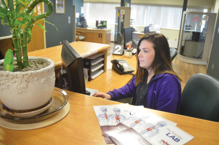 Photo by Scott McCloskey Ohio Valley Medical Center registration clerk Emily DelGuzzo works in the hospital's front lobby Monday.