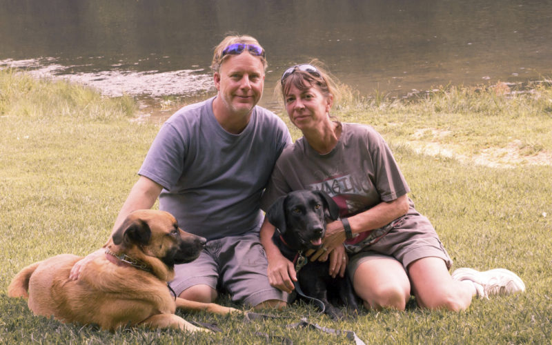 In this Aug. 22, 2015 photo provided by Amy Hunter, John and Amy Hunter are pictured with their dogs, Apollo, left, and Rubi, a black Labrador retriever, in Brown County State Park south of their home in Indianapolis, Ind. The couple lost two sons and their daughter is about to graduate from college. Amy is a stay-at-home pet mom and finds healing in her connection with their dogs. (Amy Hunter via AP)