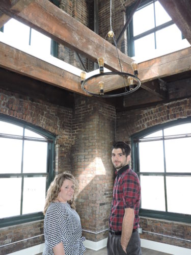 "The sixth floor ""penthouse"" at the Boury Lofts features this unique ceiling element. Woda Group officials Erica Pettrey and Daniel Archer enjoy the view."
