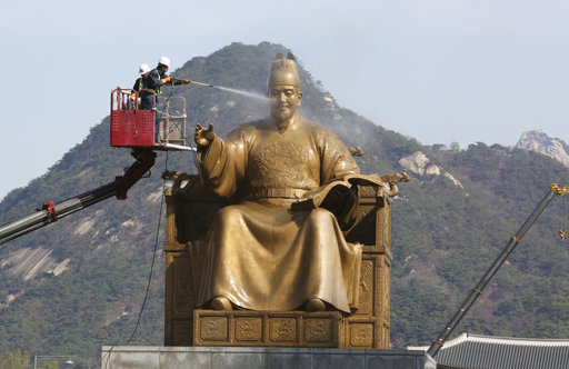 A worker sprays water onto the statue of King Sejong for a spring cleaning at the Gwanghwamun Plaza in Seoul, South Korea, Monday, April 10, 2017. King Sejong, the fourth king of the Joseon Dynasty (1392-1910), created the Korean alphabet, Hangul, in 1446. (AP Photo/Ahn Young-joon)