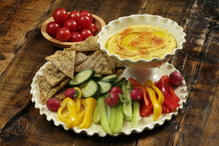 Roasted carrot hummus, with pita chips, and crudite are shown at the Institute of Culinary Education in New York. This dish is from a recipe by Elizabeth Karmel.