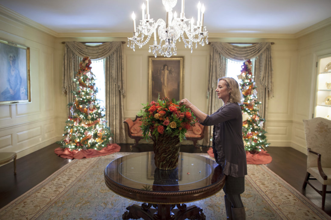 """In this Dec. 1, 2010 photo provided by Stichting Kunstboek, Laura Dowling completes a holiday arrangement of peach and coral roses in a magnolia leaf vase in the Vermeil Room, before the launch of the White House Christmas season, with the Aaron Shikler portrait of First Lady Jacqueline Kennedy in the background at the White House in Washington. The photograph is featured in the book """"Floral Diplomacy: At the White House,"""" by Laura Dowling. (Chuck Kennedy/The White House/Stichting Kunstboek via AP)"""
